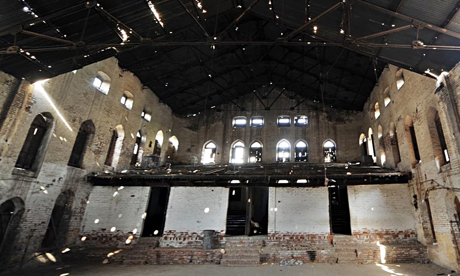 The wrecked state of the podium where the political leadership of the Indian subcontinent used to give out addresses. Below the pavilion, the gallery seats had been modified into rooms through partitions constructed by school teachers.