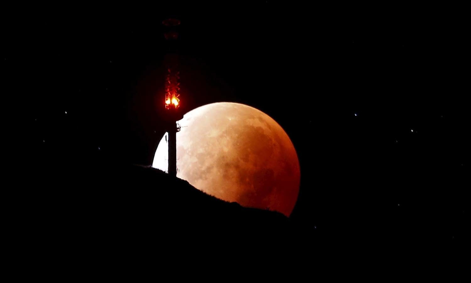 The moon, appearing in a dim red colour, is covered by the Earth's shadow during a total lunar eclipse over the peak of mount Rigi, Switzerland. — Reuters