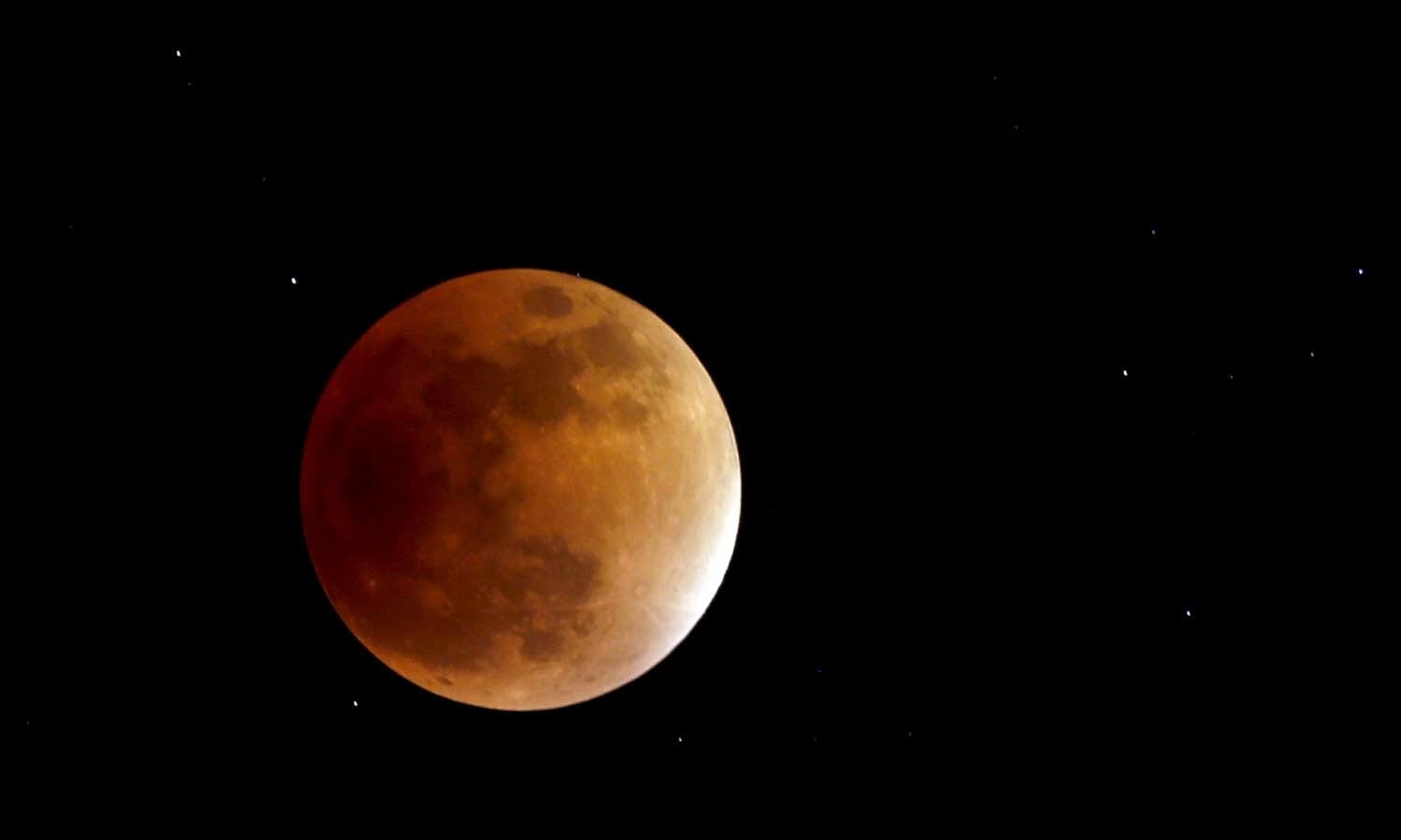 The moon, appearing in a dim red colour, is covered by the Earth's shadow during a total lunar eclipse in Bogota, Colombia. — Reuters