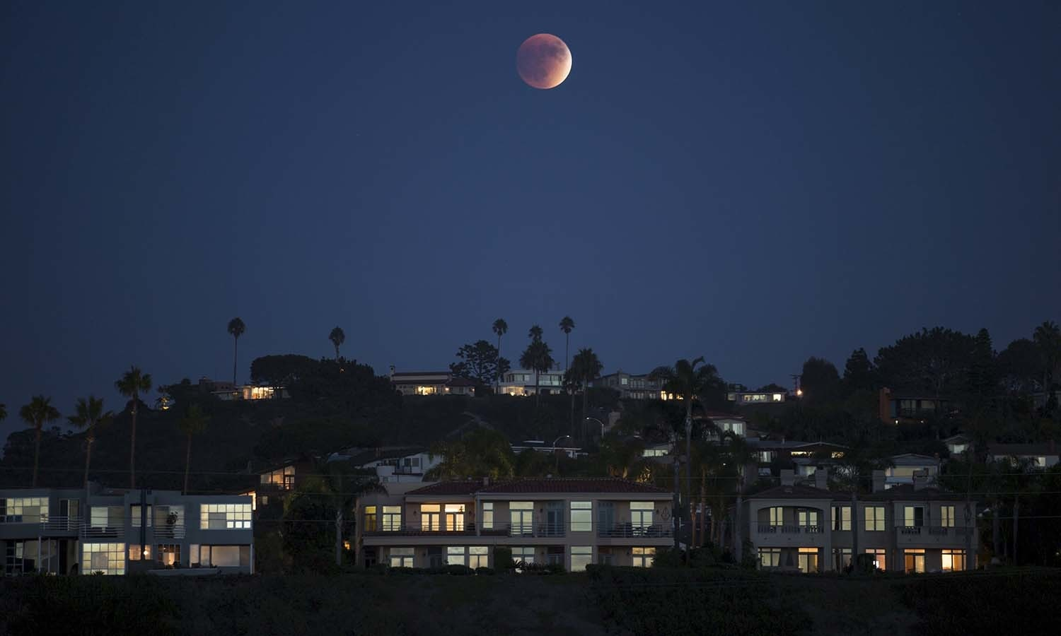 A blood moon rises behind hilltop residences in Solana Beach, California. — Reuters