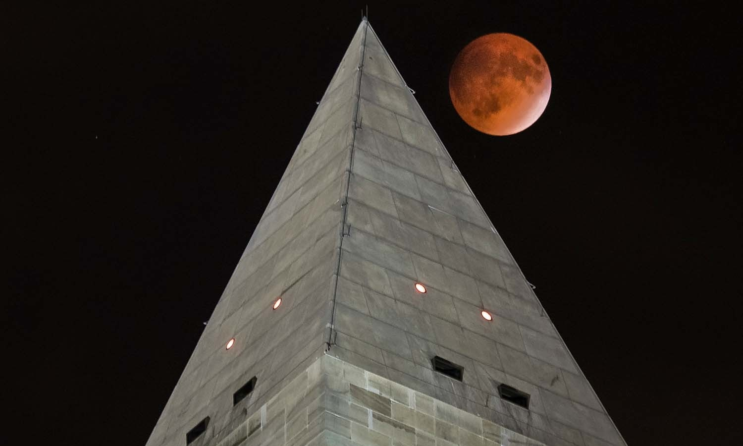 """The so-called """"supermoon"""" passes behind the peak of the Washington Monument during a lunar eclipse. — AP"""