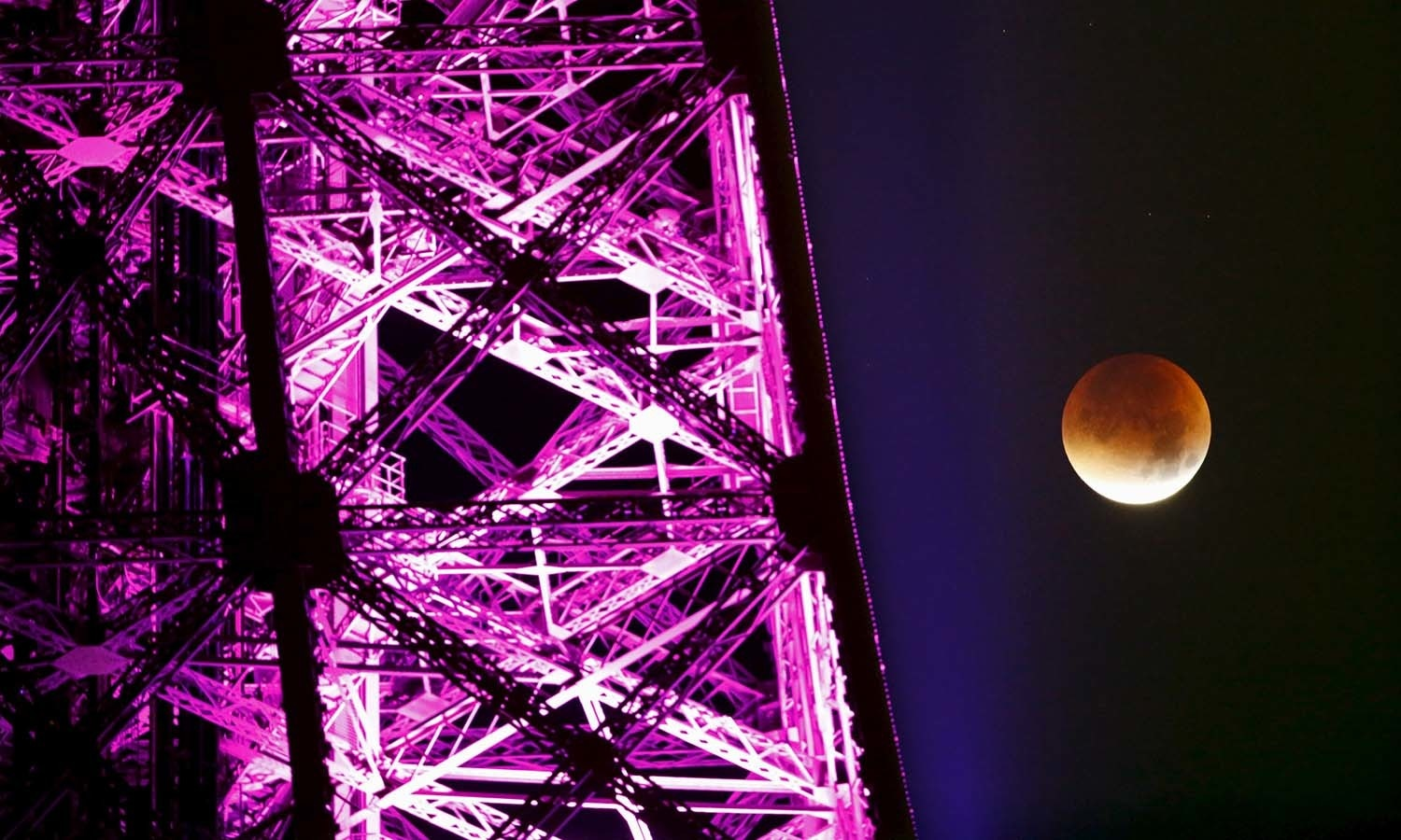 The Moon, appearing next to the Eiffel Tower in a dim red colour, is covered by the Earth's shadow during a total lunar eclipse over Paris, France. — Reuters