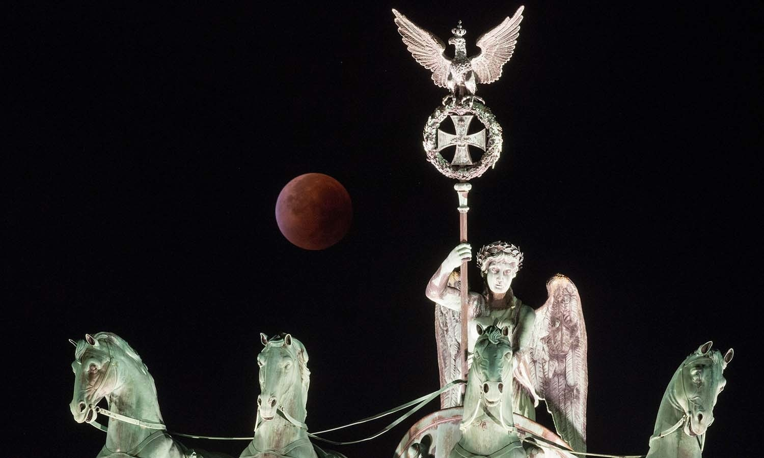 """A so-called """"blood moon"""" can be seen behind the Quadriga sculpture on top of Berlin's landmark the Brandenburg Gate during a total lunar eclipse. — AFP"""