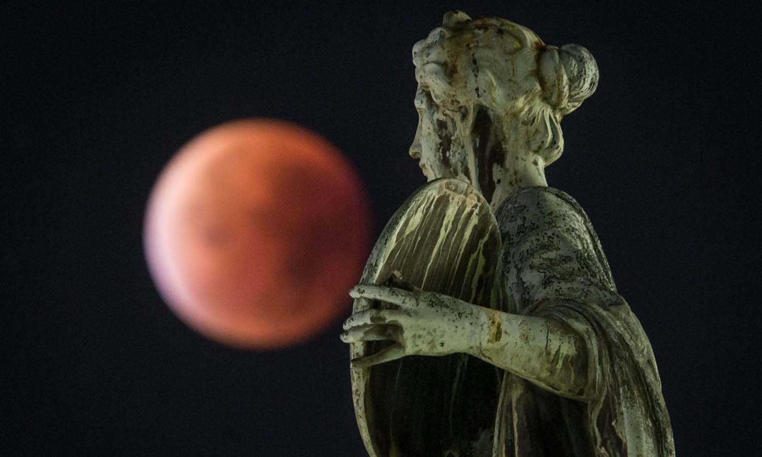 """A so-called """"blood moon"""" can be seen behind a statue during a total lunar eclipse in Frankfurt am Main, western Germany. — AFP"""