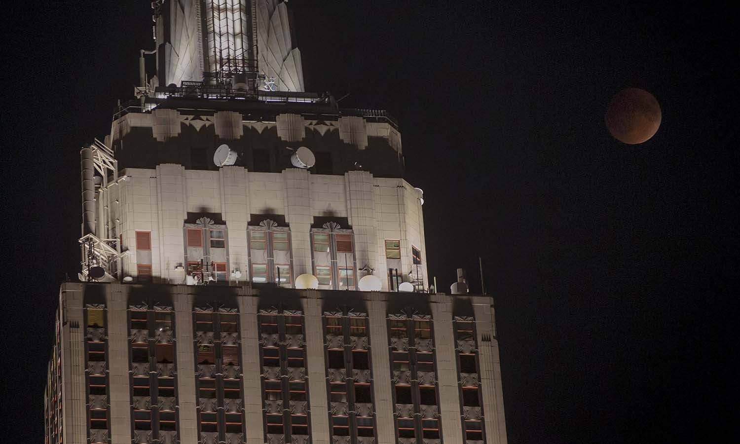 """A """"supermoon"""" is seen rising beside the Empire State Building in Manhattan, New York. — Reuters"""