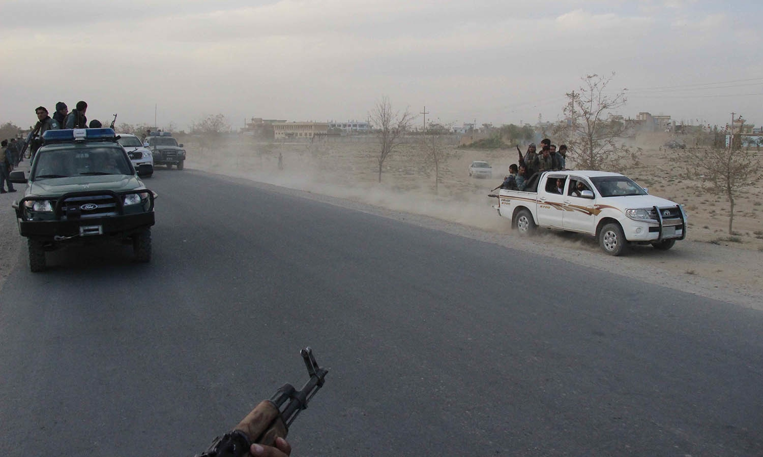 Afghan security personnel driving on a road as heavy fighting erupted near the airport on the outskirts of Kunduz. — AFP