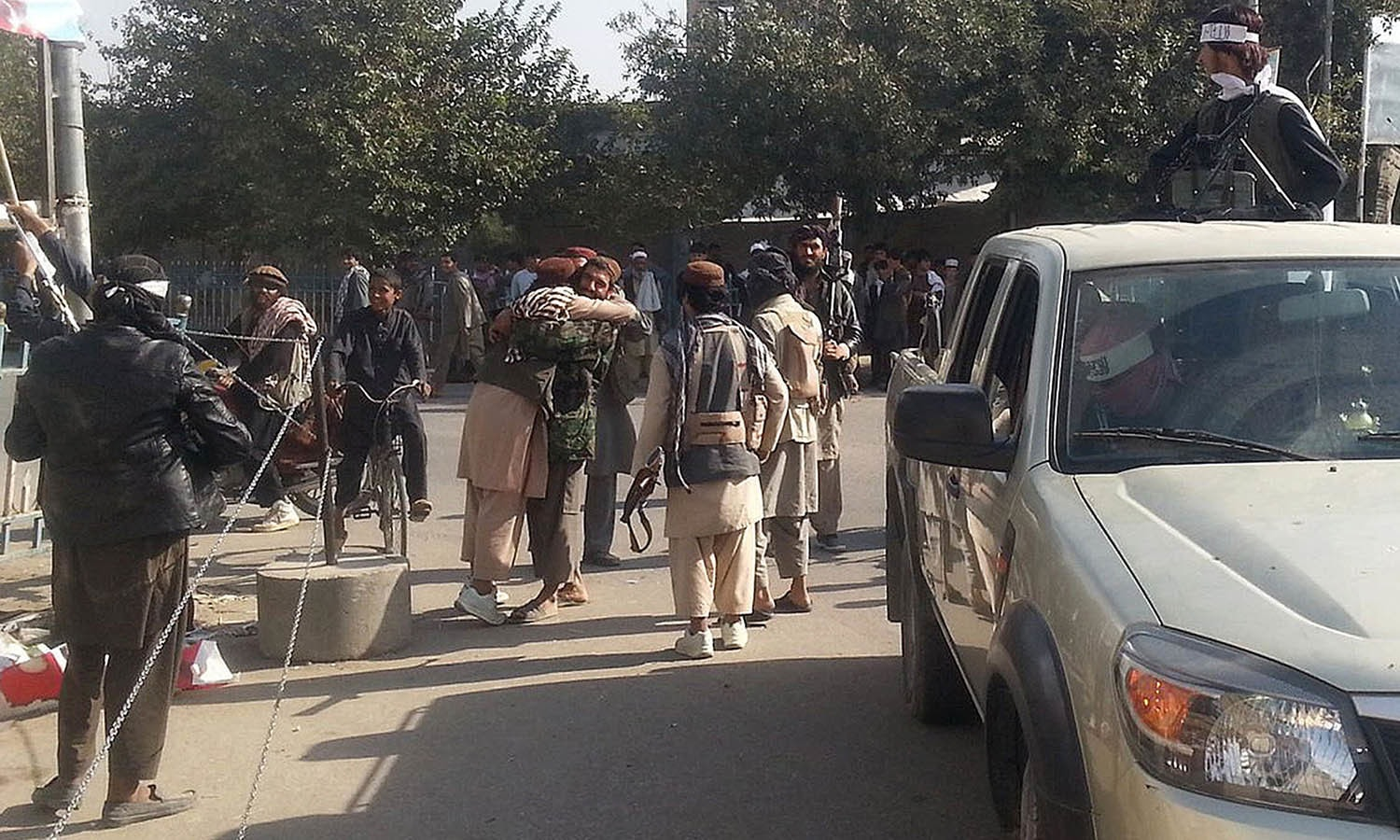 Taliban fighters hug each other a day after they overran the strategic northern city of Kunduz. — AFP