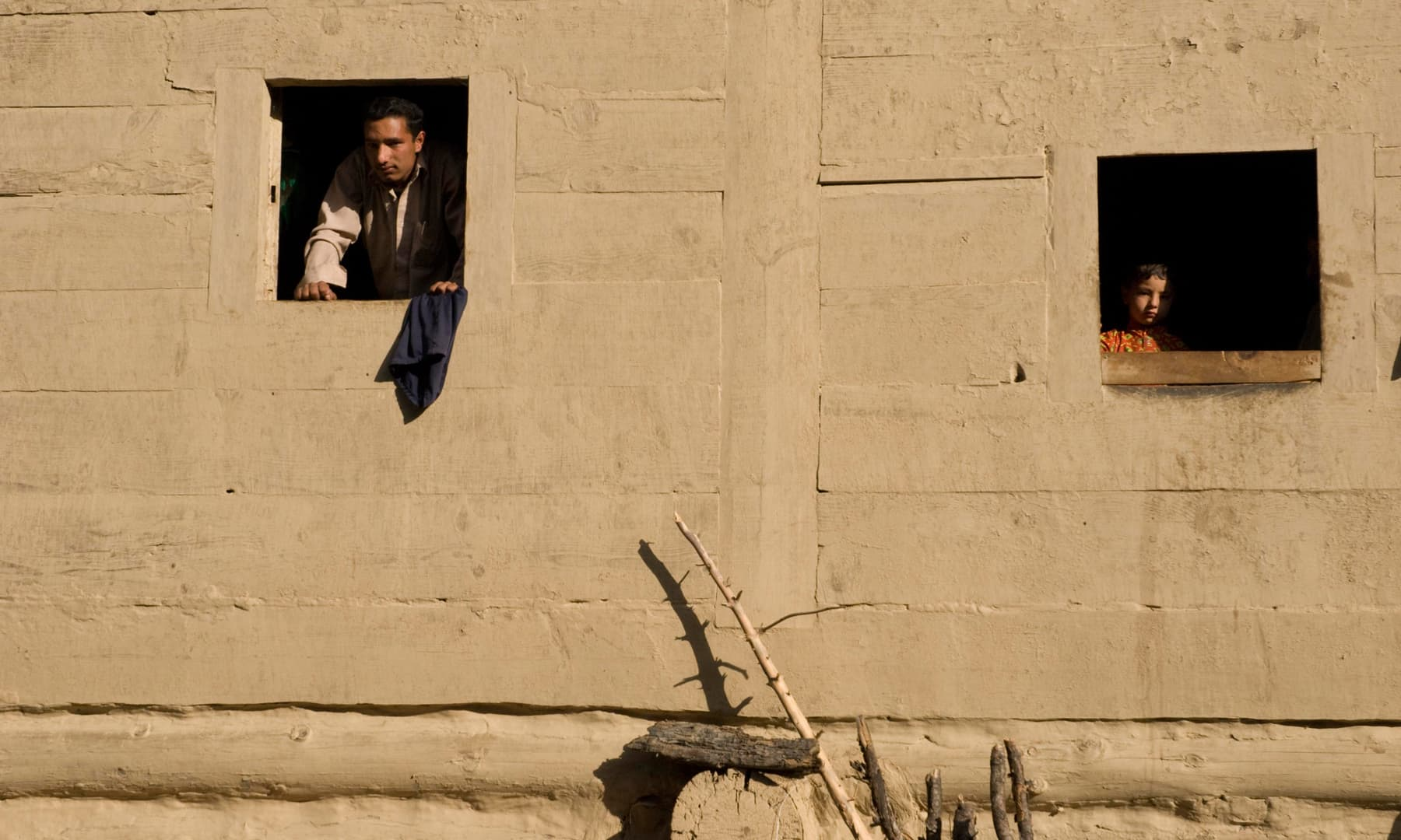 A man and child look out the windows of a wooden house in Taobat | Ayesha Villani, White Star