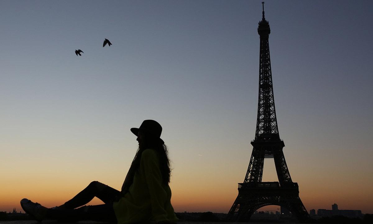 ایفل ٹاور، پیرس کے سامنے ایک خاتون پوز کرتے ہوئے—۔فوٹو/ اے ایف پی