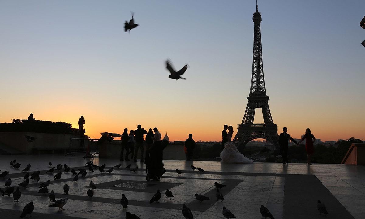 ایفل ٹاور، پیرس کے قریب ٹروکیڈرو پلازہ پر ایک نیا شادی شدہ جوڑا فوٹو شوٹ کرواتے ہوئے، تصویر میں کبوتروں کو بھی اڑے ہوئے دیکھا جاسکتا ہے—۔فوٹو/ اے ایف پی