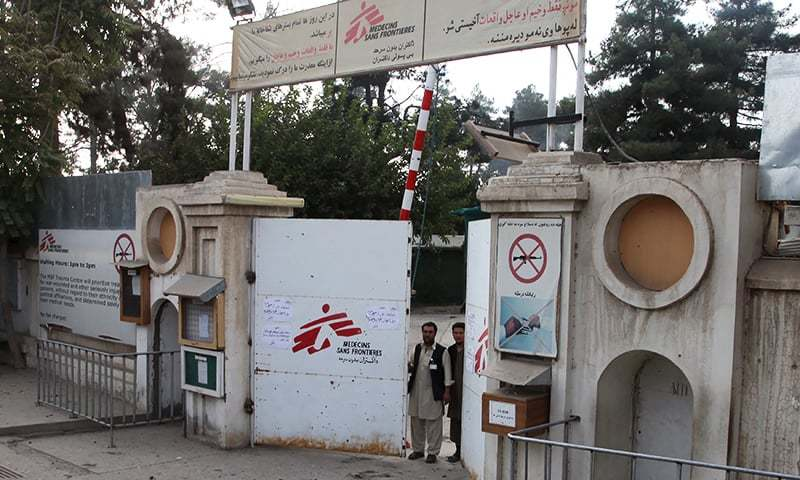 Afghan guards stand at the gate of Medecins Sans Frontieres (MSF) hospital after an air strike in the city of Kunduz, Afghanistan. — Reuters