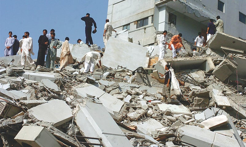 Following an earthquake, Pakistani rescue workers and volunteers gather at a collapsed building in Islamabad. —AFP