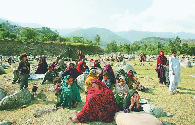 Earthquake victims wait under the open sky for rescue and relief. —AFP