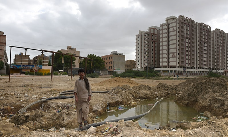 In this photograph taken on August 20, 2015, a boy walks past a closed illegal hydrant in Karachi.  — AFP