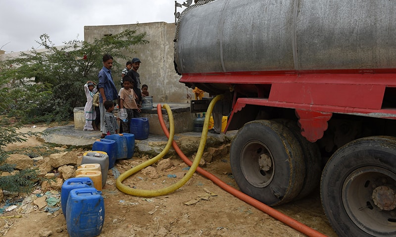 In this photograph taken on August 22, 2015, residents fill containers with water from a government water tanker in a slum area of Karachi. — AFP