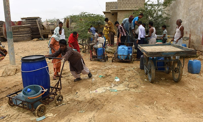 In this photograph taken on August 22, 2015, residents fill containers with water provided by the government in a slum area of Karachi.   — AFP