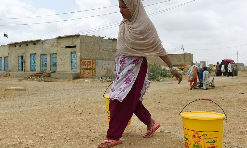 In this photograph taken on August 22, 2015, a woman carries a bucket filled with water in a slum area of Karachi. — AFP