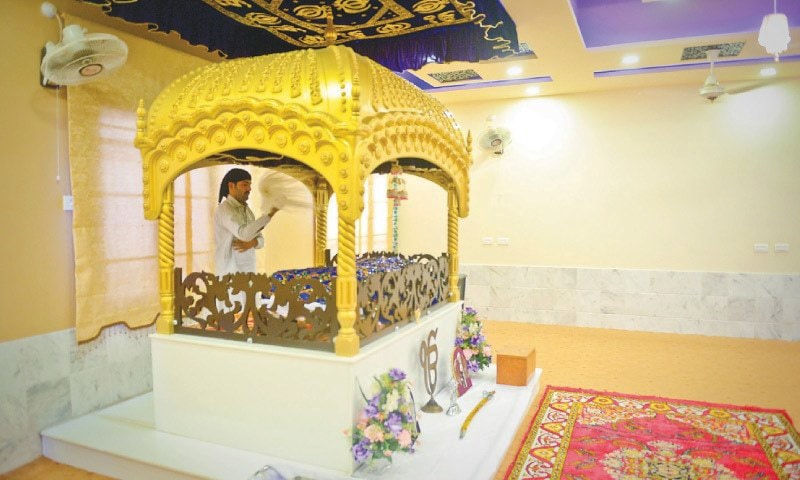 A worshipper reverently fans the Guru Granth Sahib with a fly whisk  in Gurdwara Shah which opened to the public in Bhit Shah on Sept 4. —Fahim Siddiqi / White Star
