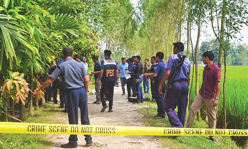 Policemen stand guard at the site where Japanese national Hoshi Kunio was shot to death on Saturday in Kaunia town, Bangladesh.—AFP