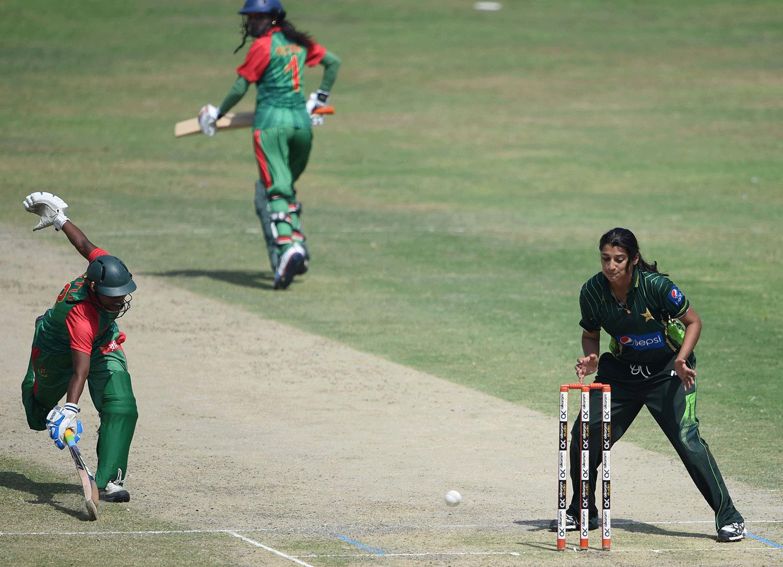 Bangladesh's Ritu Moni (L) stretches to make her ground as Pakistan's Asmavia Iqbal looks on. — AFP