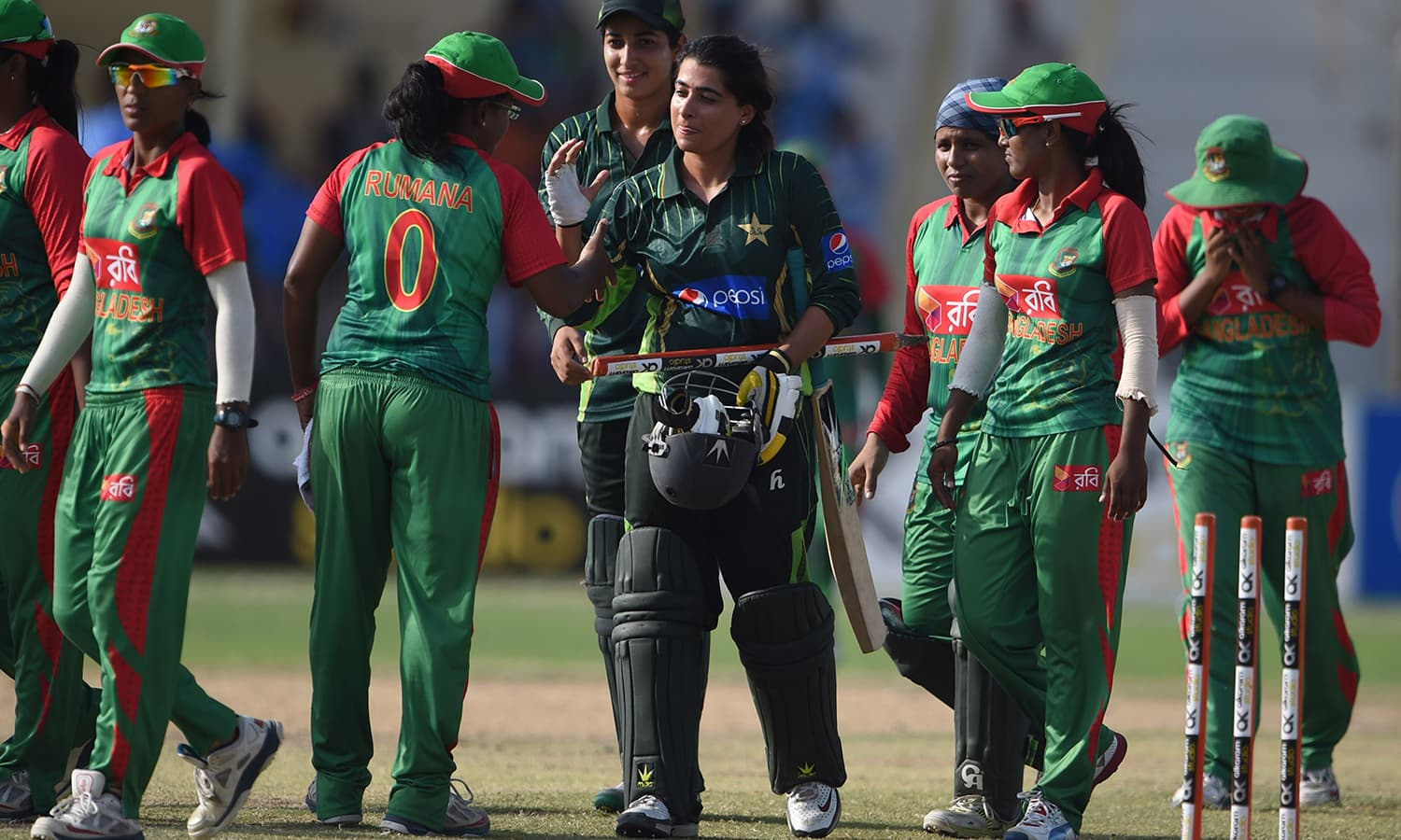 Pakistani captain Sana Mir (C) shakes hands with Bangladesh's Rumana Ahmed after winning the series. — AFP