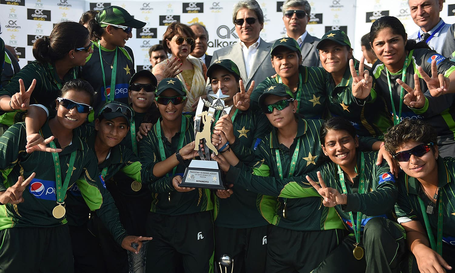 The triumphant Pakistan team poses with series trophy. — AFP