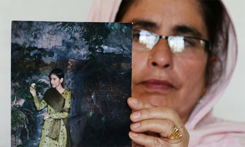 Nazish Naz's mother, Gulnaz, holds up a photo of her missing daughter. ─ AFP