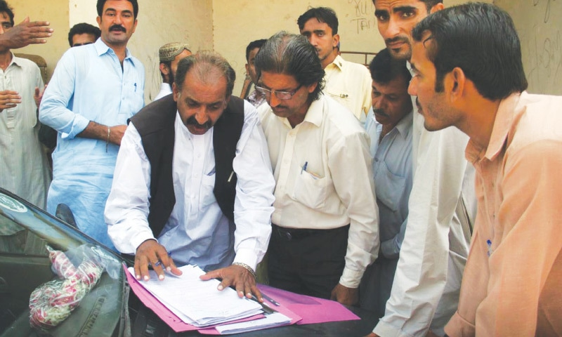 A candidate examines his nomination papers for the local government elections, scheduled to be held in Karachi on Dec 3, before filing them at the deputy commissioner's office on Wednesday.—Online