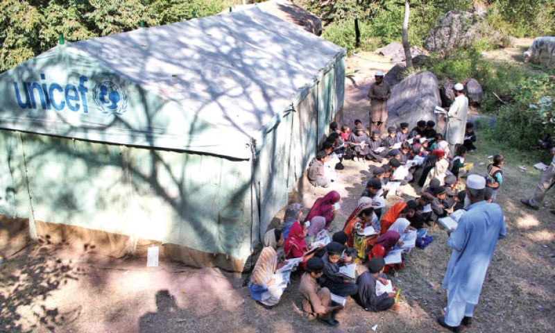 Students of a government primary school attend class outside a tent in Balakot provided by Unicef. The school building was destroyed in the 2005 earthquake. — Online
