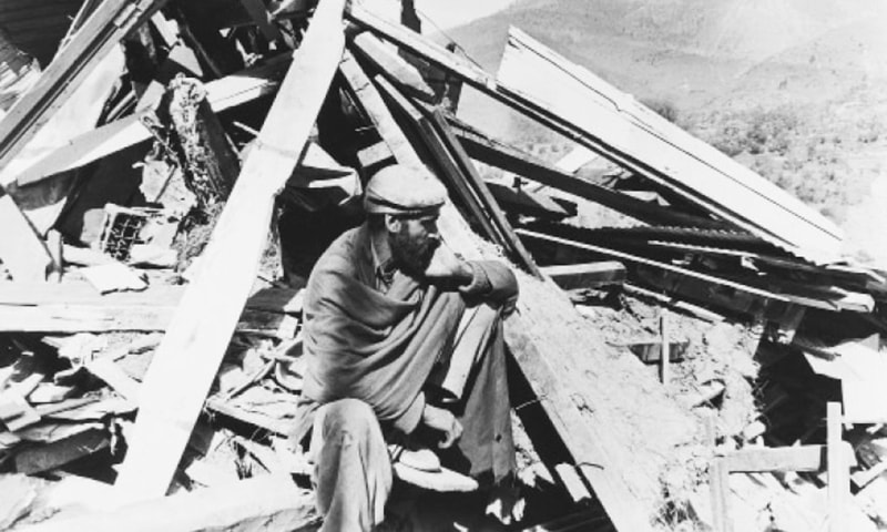 A man sits on the rubble of his destroyed home in the Koutch e Syeda area of Azad Kashmir.—White Star