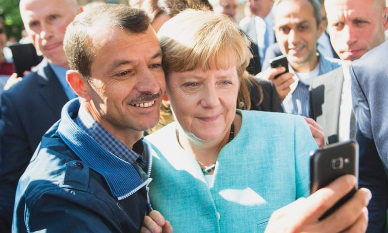 ایک تارکِ وطن جرمن چانسلر اینجلا مرکل کے ساتھ سیلفی لے رہا ہے.