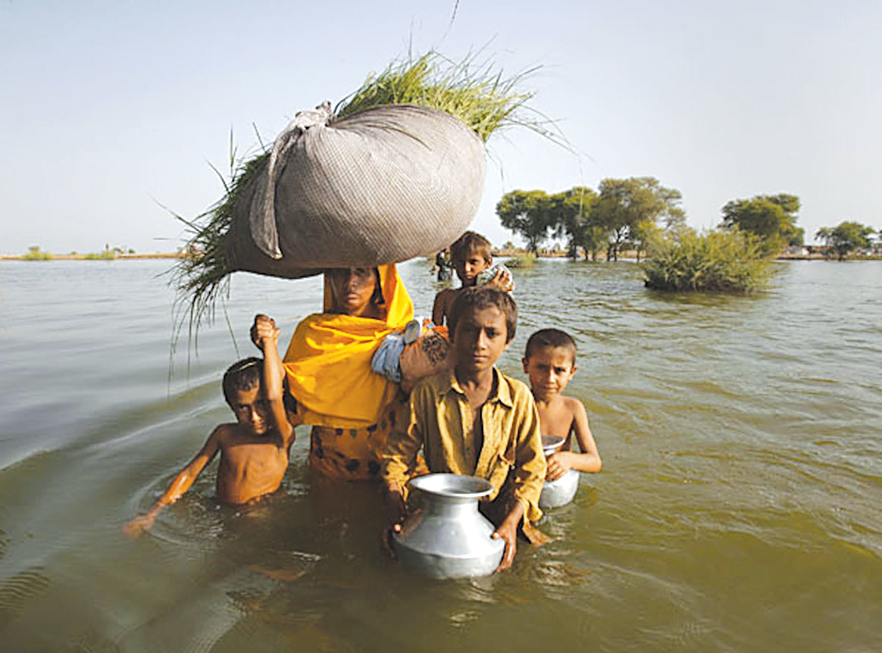 Climate change will lead to more natural disasters and a rise in sea level. A family displaced by flooding wades through flood waters in Bello Patan, Sindh. — Reuters