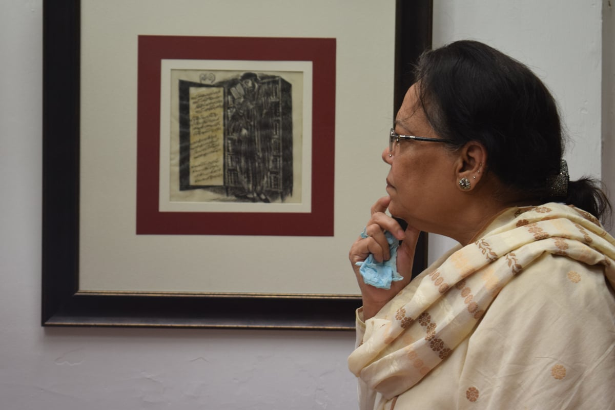 A visitor looks intently at one of the paintings. — Photo by Yumna Rafi