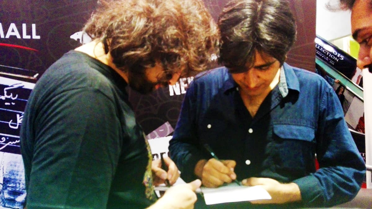 Ali Noor signs an album for fans with Ali Hamza. — Publicity Photo