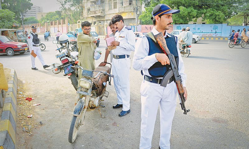 Wearing bulletproof vest, a traffic sergeant stands alert with a Kalashnikov rifle as his colleagues perform routine work on a busy road.—White Star