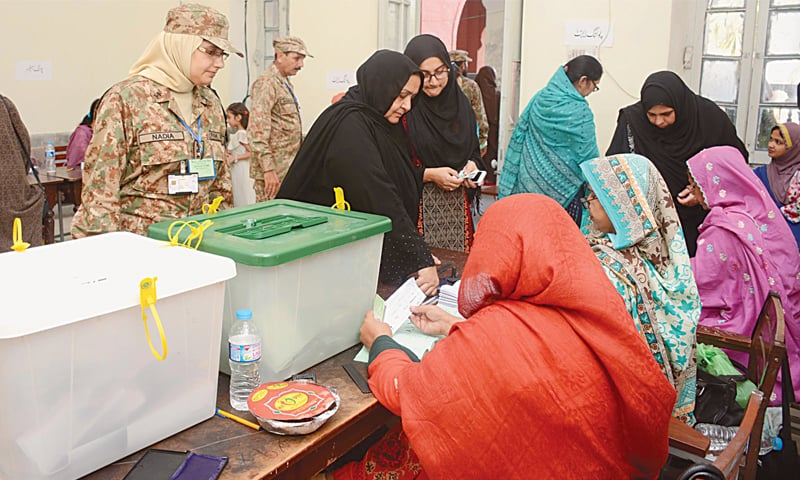 LAHORE: An army soldier stands guard as women line up to cast their vote for NA-122 on Sunday.—White Star