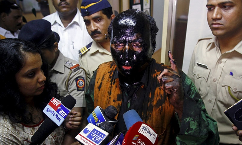 Sudheendra Kulkarni, chairman of the Observer Research Foundation Mumbai, with his face smeared with black ink, speaks to journalists in Mumbai ─ Reuters