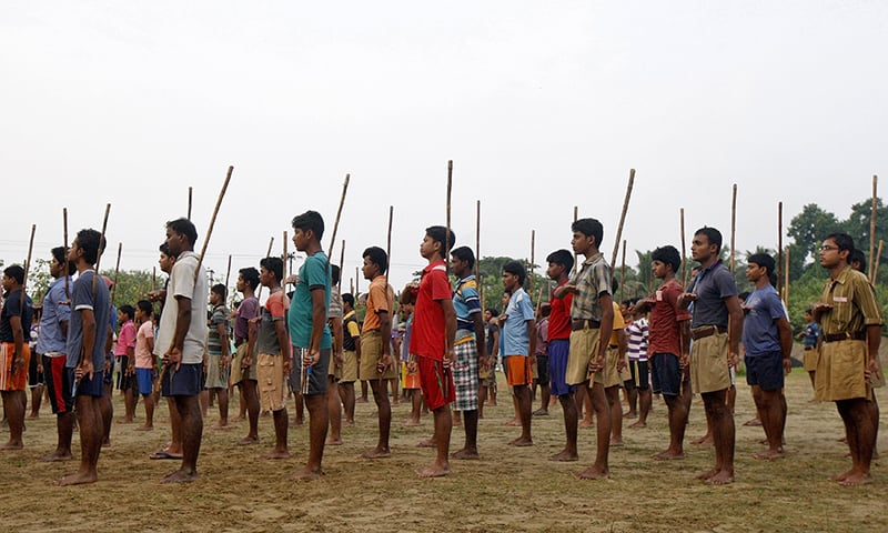 RSS volunteers hold sticks as they pray during a training session at Tatiberia village in West Bengal, India. — Reuters