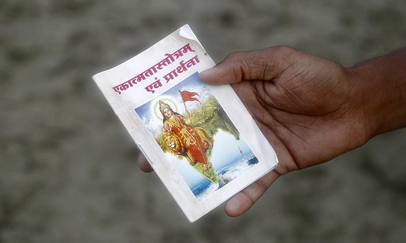 An RSS volunteer holds a prayer book during a training session at Tatiberia village in West Bengal, India. — Reuters