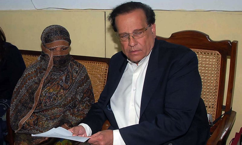 Former Punjab governor Salman Taseer handing over a document to Asia Bibi, who was sentenced to hang in Punjab in 2010 after being found guilty of committing blasphemy. — AFP/file