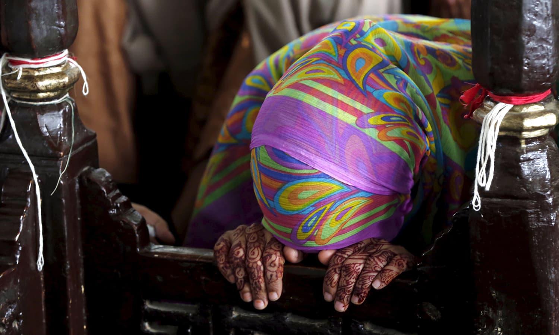 A woman prays at the shrine of Hasan-al-Maroof Sultan Manghopir, better known as the crocodile shrine. —Reuters