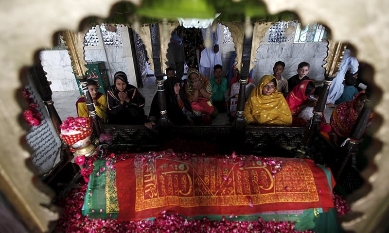 Devotees pray at the grave while visiting the shrine of Hasan-al-Maroof Sultan Manghopir, better known as the crocodile shrine, on the outskirts of Karachi. —Reuters