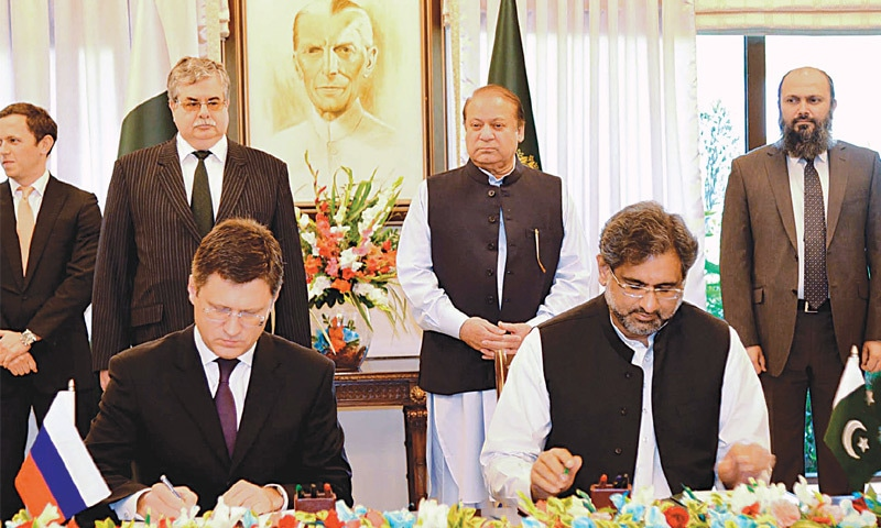 ISLAMABAD: Petroleum Minister Shahid Khaqan Abbasi and Russian Energy Minister Alexander Novak sign an agreement for the North-South Gas Pipeline project as Prime Minister Nawaz Sharif looks at a ceremony here  on Friday.—AFP