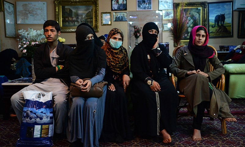In this photograph taken on October 10, 2015, an Afghan family, who have been displaced from the northern Afghan city of Kunduz during clashes between Afghan security forces and Taliban insurgents, speak as they gather at a temporary shelter donated by a businessman at a hotel in Kabul. — AFP
