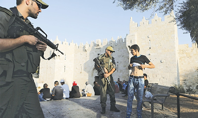 OCCUPIED JERUSALEM: Israeli policemen order a Palestinian man to lift his shirt near the Damascus Gate on Saturday.—Reuters