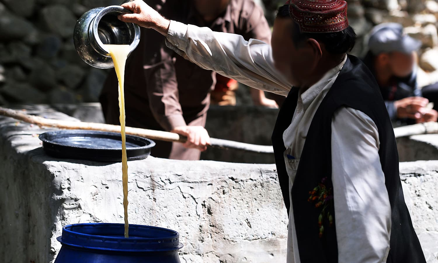 A local pours the juice from crushed grapes as part of a brewing wine process in a garden in the remote village. ─ AFP