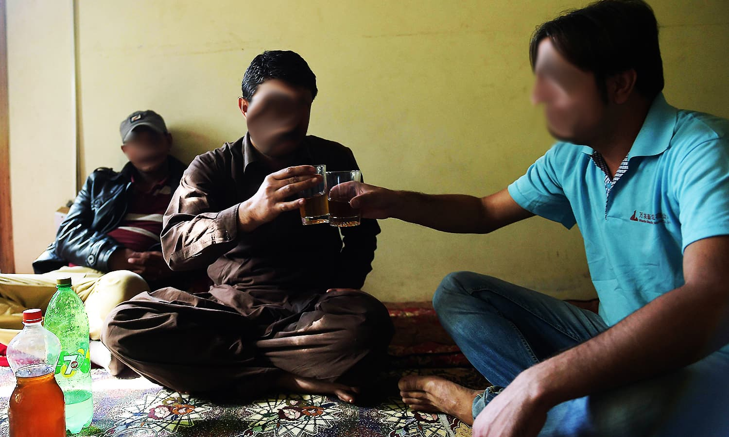 Ahsan and his cousin toast each other as they prepare to drink home brewed wine. ─ AFP