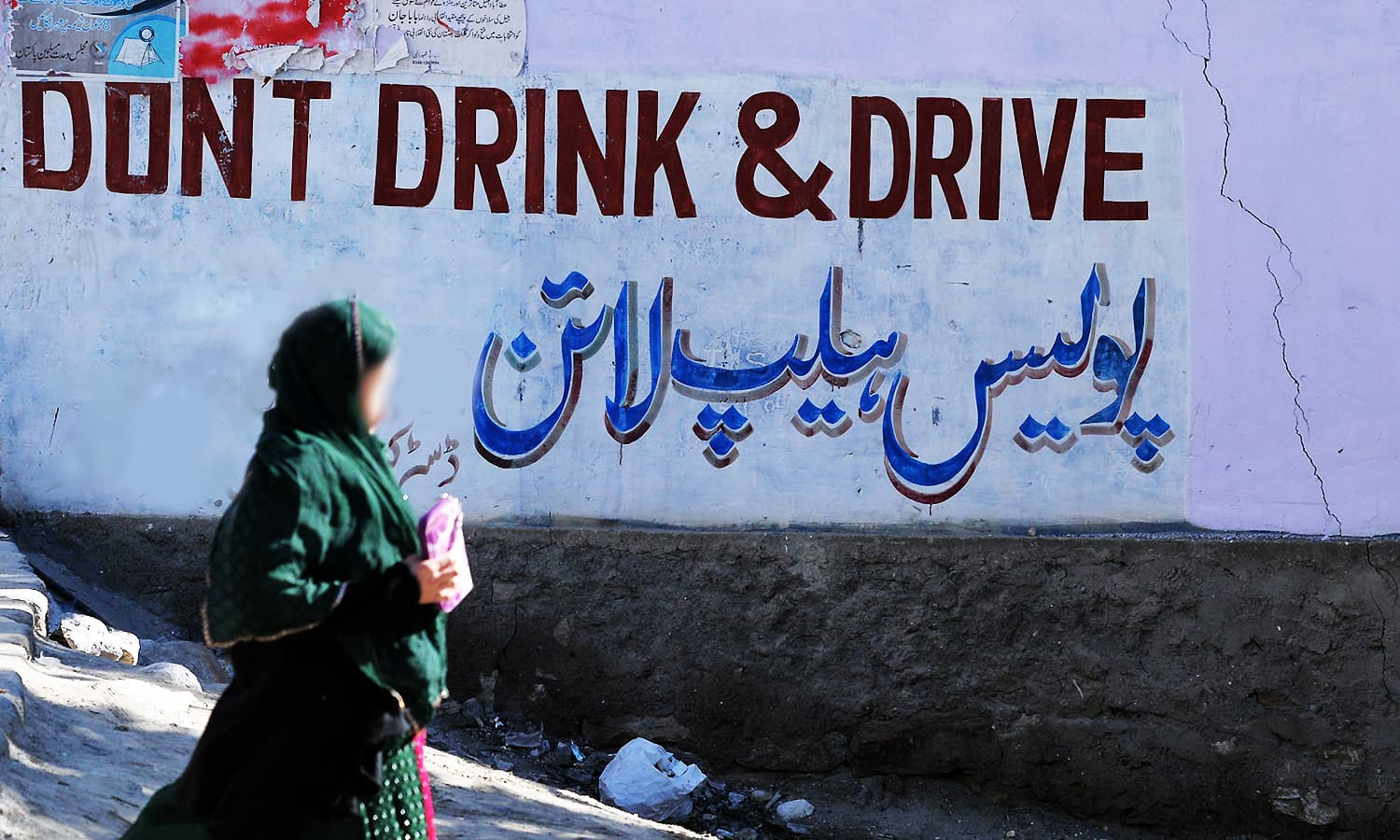 """A woman walks past a sign pasted by authorities that says """"Don't Drink and Drive"""". ─ AFP"""