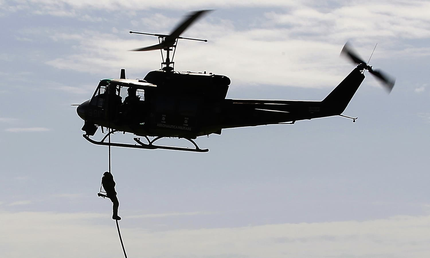 A soldier is airdropped from an Italian air force AB212 helicopter during the Nato Trident Juncture exercise 2015, in Trapani, Italy. — AP