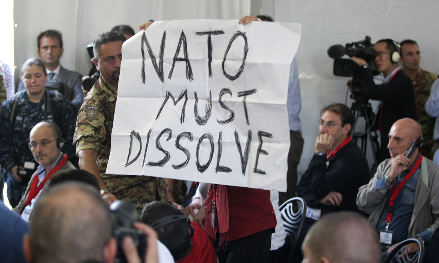"A protestor shows a poster reading ""Nato Must Dissolve"" during a press conference following the opening ceremony of Nato's large scale exercise Trident Juncture 2015 at the Italian Air Force Base in Trapani, Sicily. — AFP"